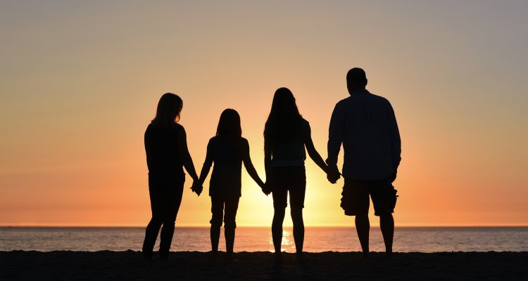 Family of four watching sunset