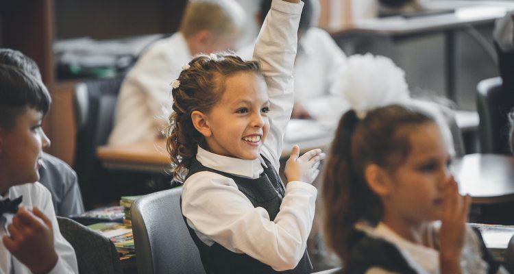 Girl attending school raising her hand