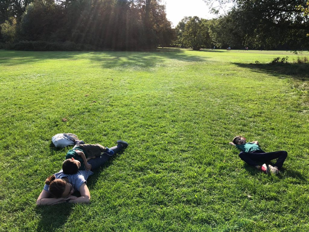 Parent and children lying on the grass
